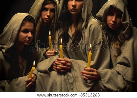 Four nuns praying with candles in their hands