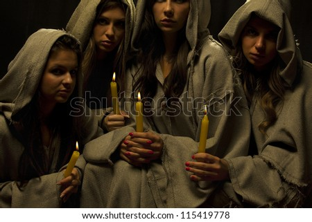 Four nuns preying with candles in their hands