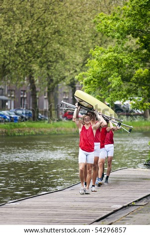 Four oarsmen carrying a rowing boat back to the boathouse after winning a race.