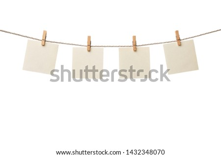 Photo of  Four old paper blank notes hanging on the rope with wooden clothespins isolated on white background