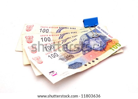 Four one hundred South African Rand held with a blue office clip. Image isolated on white background.