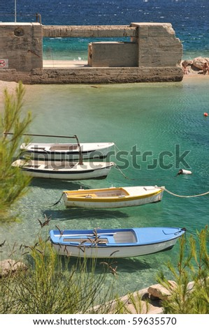 Four open boats at anchor by a beach.