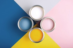 Four open cans of paint on bright symmetry background. Yellow, white, pink, blue colors of paint. Place for text. Renovation concept.