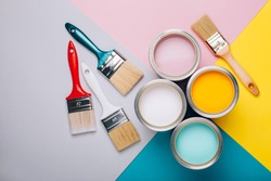 Four open cans of paint with brushes on bright background. Yellow, white, pink, turquoise colors of paint. Vertical photo. Renovation concept.