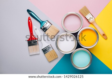 Four open cans of paint with brushes on bright background. Yellow, white, pink, turquoise colors of paint. Vertical photo. Renovation concept. Foto d'archivio ©