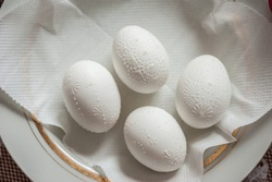 Four painted eggs on the plate. Eggs prepared for painting with food coloring. Easter Egg decorating. Close up, soft focus. Step of painting process.