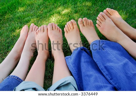 Four pairs of bare feet in the grass