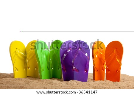 Four pairs of colorful flip-flop sandals on a beach background, studio shot