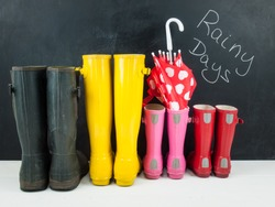 four pairs of colorful rubber rain boots  and a childs umbrella on a white rustic floor in front of a blackboard with the text rainy days