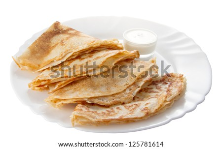 four pancakes with sour cream on a white plate (isolated object)