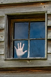 four paned window in a wooden wall with a person's hand pressed against one pane as if trying to escape.