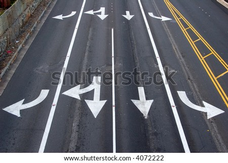 Four paved lanes with traffic arrows directing traffic in various directions