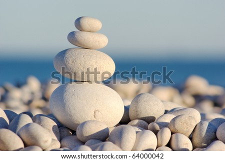 Four pebbles balancing on a beach. Harmony, Teamwork or Meditation. Narrow depth of field with point of sharp focus on the smaller pebbles at the top.  Converted from RAW with minimal sharpening.