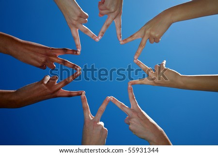 Four people holding their hands to a star shape