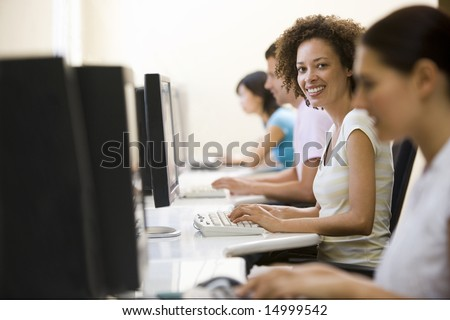 Four people in computer room typing and smiling #14999542