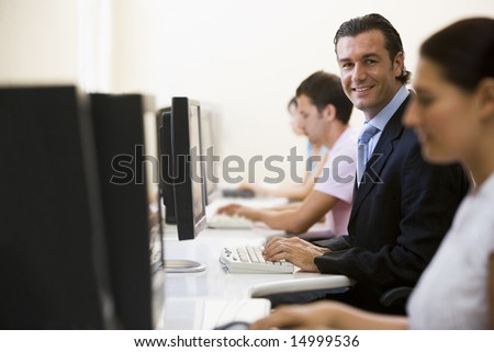 Four people in computer room with one man wearing a suit smiling