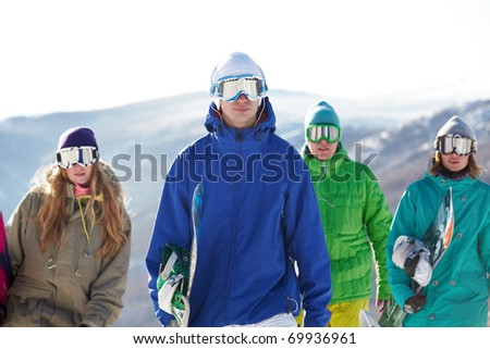 Four people in ski goggles carrying snowboards - stock photo