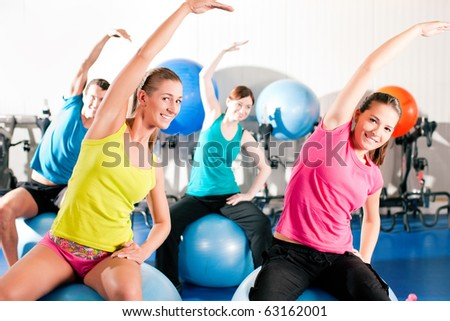 Four people - man and women - in the gym doing gymnastics on an exercise ball