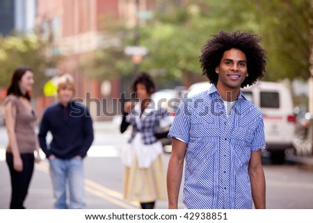 Four people on city street with young male as focus. Horizontally framed shot.