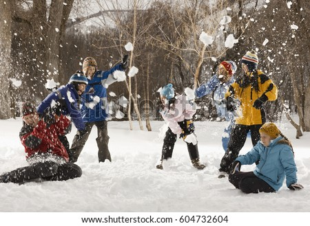 Four people outdors in hats, coats and scarves, having an energetic snowball fight,