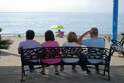 Four people sitting on a bench on the promenade looking at the sea and a person taking a sun bath under a parasol