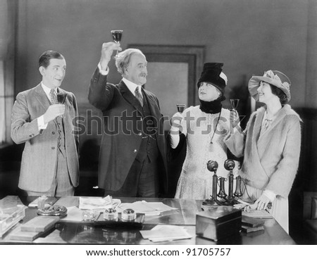 four people toasting with wine