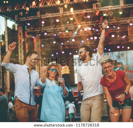 Four people, two women and two men are dancing on concert. They are on festival which is happening in their city.  #1178728318