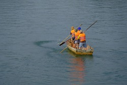 four peoples are rowing across the green river on holiday
