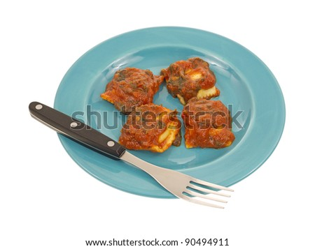 Four pieces of ravioli on a blue plate with fork on a white background.