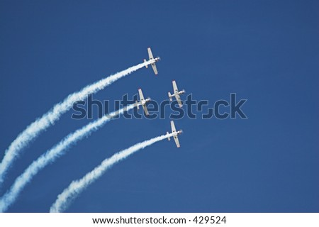Four planes fly in formation with vapor trails