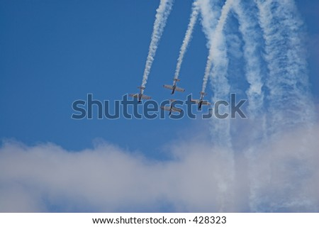 four planes fly  in formation with vapor trails against a brilliant blue sky - stock photo
