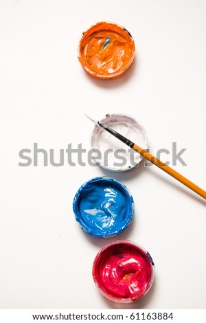 Four plastic covers with color paints and paintbrush, isolated on white, view from above