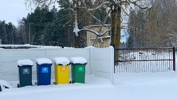 Four plastic trash cans with garbage near the fence in winter. The containers are located in the courtyard of the residential area. Separate waste sorting. Responsible attitude to the environment.