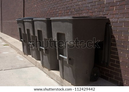Four plastic trash dumpsers in an alley - stock photo