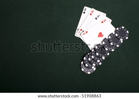 Four poker aces and black chips on green. Gambling concept