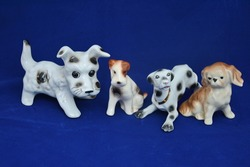 four porcelain dogs on blue background