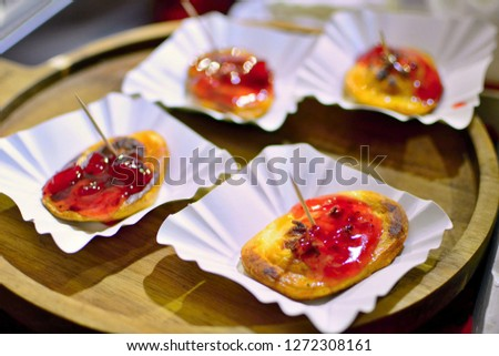 Four portions of grilled oscypek (traditional smoked cheese made of sheep milk) with cranberries serving on wooden plate.