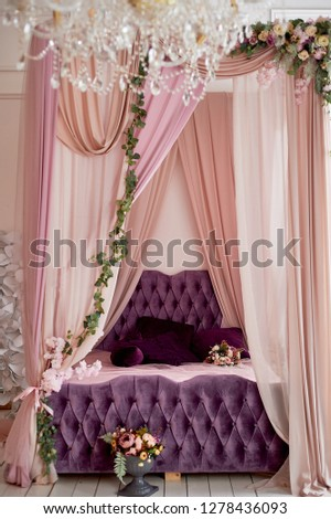 Four-poster bed in a bright interior in pink and purple tones