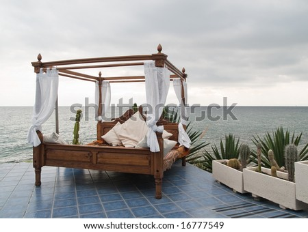 Four poster bed on patio by the sea
