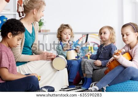Four preschoolers having fun in kindergarten playing the instruments #635590283