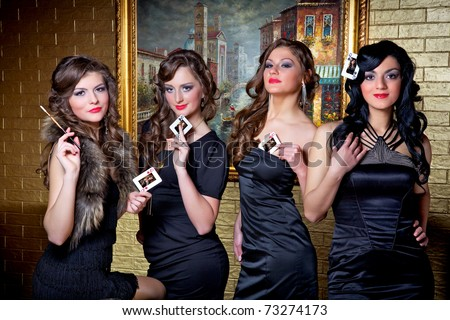 Four queens of poker: a spade, a heart, a diamond and a club. Four beautiful girls play poker.