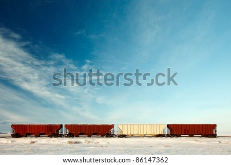 Four railroad hopper cars parked on rural tracks all by themselves on a cold winter day.