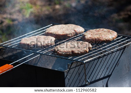 Four raw Hamburgers on Barbeque Grill with smoke