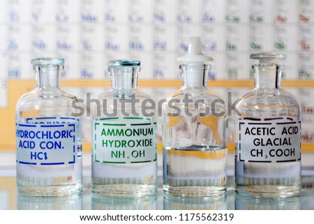 Four reagent bottles containing hydrochloric acid, ammonium hydroxide, water and acetic acid.
