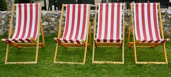Four red and white striped deckchairs in the garden