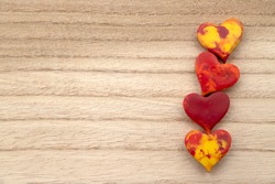 Four red and yellow Melted Wax crayon hearts in a row on a wood grain background with copy space