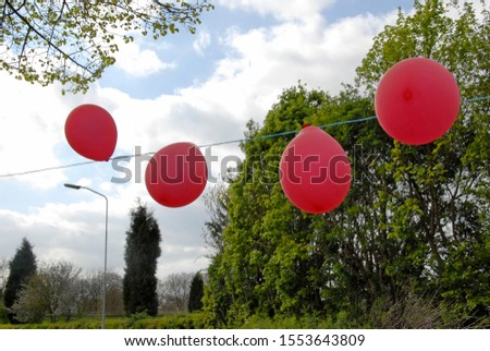 four red balloons hanging outside on a outside party