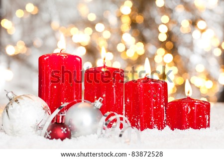 four red candles with christmas balls in snow and lights background for  advent