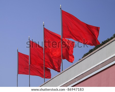 Four red flags waving brightly in the afternoon sun on the top of the memorial to Mao Tse Tung at Tianenmen Square in Beijing.