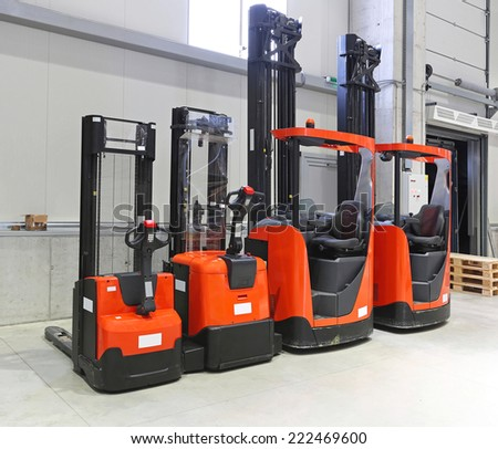 Four red forklift trucks in distribution warehouse